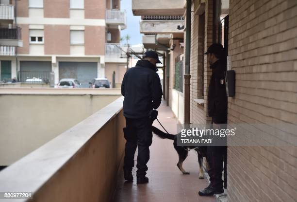 Italian carabinieri patrol with a sniffer dog on November 28 2017 during searches in Ostia Rome's seaside district where the Spada clan lives...