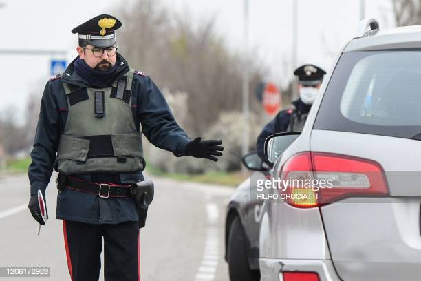 Italian Carabinieri police officers hold a road check point at the border between the quarantined provinces of Modena and Bologna on March 9 2020 in...