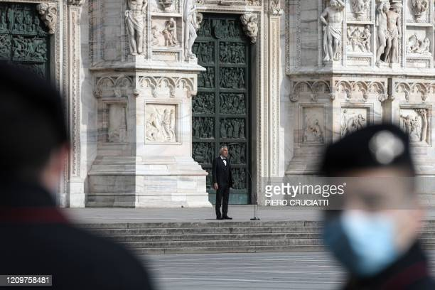 Italian Carabinieri policemen stand by as Italian tenor and opera singer Andrea Bocelli sings during a rehearsal on a deserted Piazza del Duomo in...