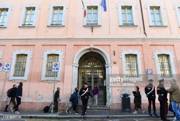 Italian Carabinieri policemen stand guard outside the 'Giovanni Vailati' secondary school as pupils arrive for class on March 21 2019 in Crema east...