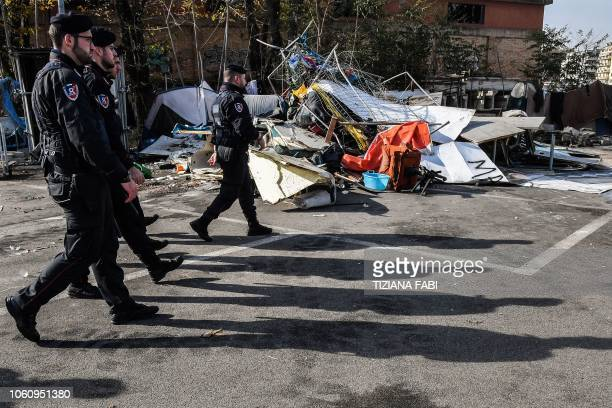 """Italian Carabinieri policemen walk across a makeshift migrants' camp known as """"The Baobab"""" during the camp's eviction by police forces in Rome on..."""