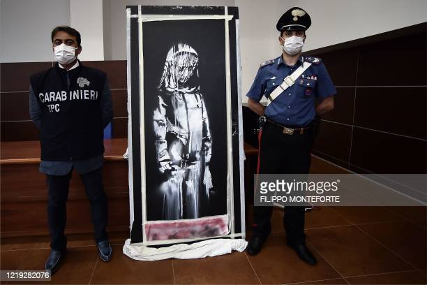 TOPSHOT Italian Carabinieri pose near a piece of art attributed to Banksy that was stolen at the Bataclan in Paris in 2019 and found in Italy during...