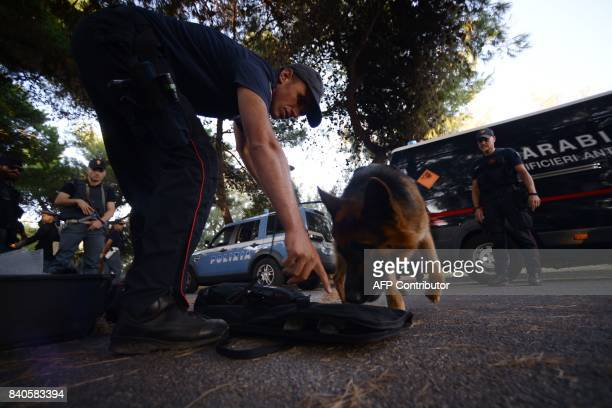 Italian Carabinieri work with a sniffer dog to check luggages near the entrance of the 74th Venice Film Festival on August 29 2017 at Venice Lido The...