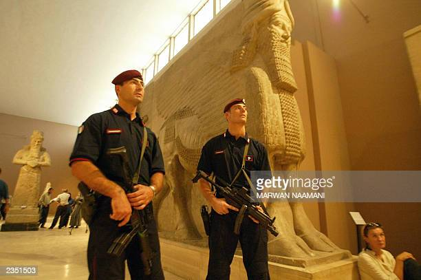 Italian Caribiniere stand guard during the opening of the first exhibition of the 'Treasures of Nimrud' at Baghdad's National Museum 03 July 2003 in...