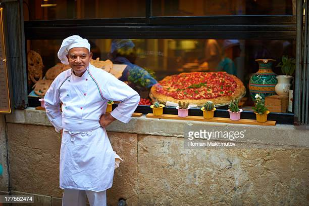 Italian chief cook standing outside his pizzeria. Giant pizza presented in showcase.