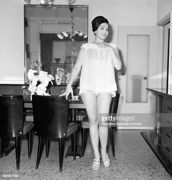 Italian circus queen and actress Moira Orfei posing leaning against the table in babydoll in her living room at home Italy 1956