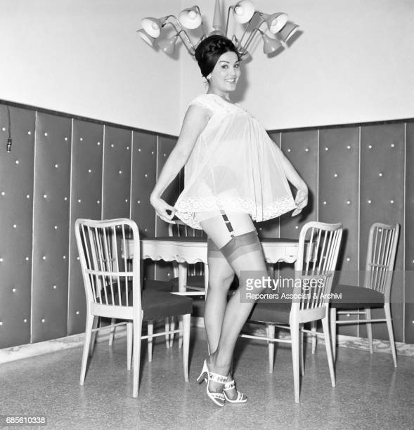 Italian circus queen and actress Moira Orfei showing off her babydoll beside the table in her living room at home Italy 1956