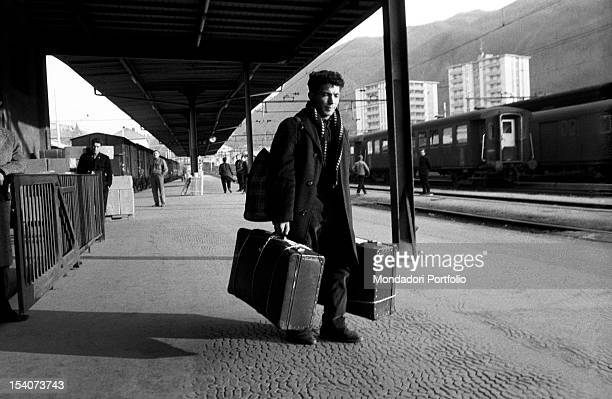 Italian citizen who emigrated to Switzerland with suitcases in hand waiting for a train station Switzerland the sixties