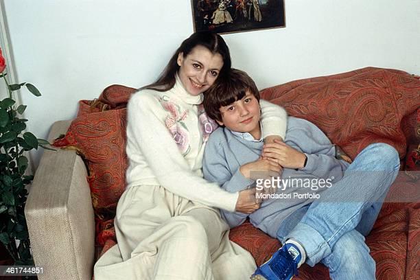 Italian classical ballet dancer Carla Fracci hugging her son Francesco Menegatti on the sofa 1982