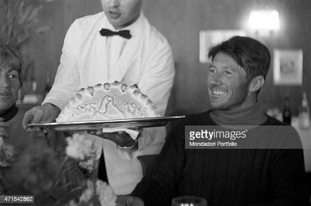 'Italian climber Walter Bonatti celebrating at the restaurant his winter solo ascent on the North wall of Monte Cervino A waiter is bringing a cake...