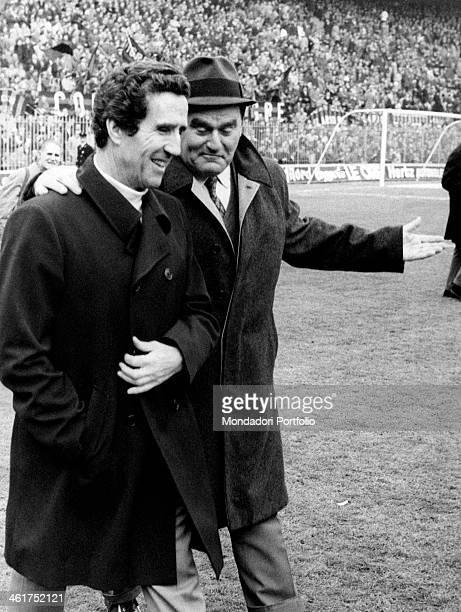 Italian coach Nereo Rocco walking on a football ground with Argentinianborn French coach Helenio Herrera 1972