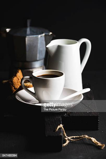 Italian coffee breakfat set. Cup of hot espresso, creamer with milk, cantucci and moka pot and cookies on dark rustic wooden board over black background