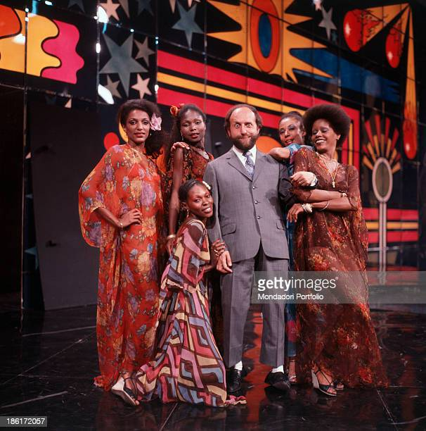Italian comedian and actor Enrico Beruschi posing among the members of tropical and Caraibic music band Chocolat's on the set of the TV show Non stop...