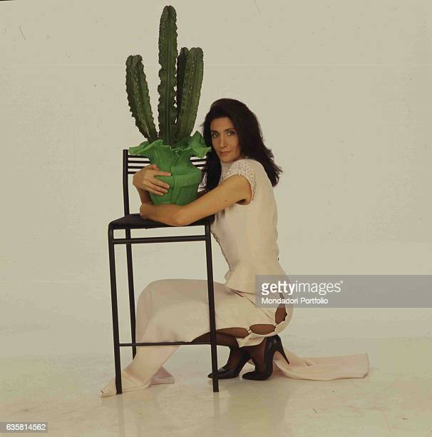 Italian comedian Anna Marchesini posing crouching and hugging a vase with a cactus resting on a high stool. Studio photo shooting. Italy, 1995