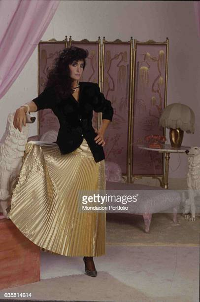 Italian comedian Anna Marchesini posing in an elegant suit for a photo shooting. Behind her, a screen and a chiase longue. Italy, 1986