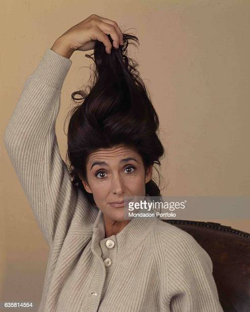 Italian comedian Anna Marchesini posing lifting up her hair for a studio photo shooting. Italy, 1998