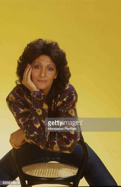 Italian comedian Anna Marchesini posing seated on a stool resting her arms on the back for a studio photo shooting. Italy, 1985