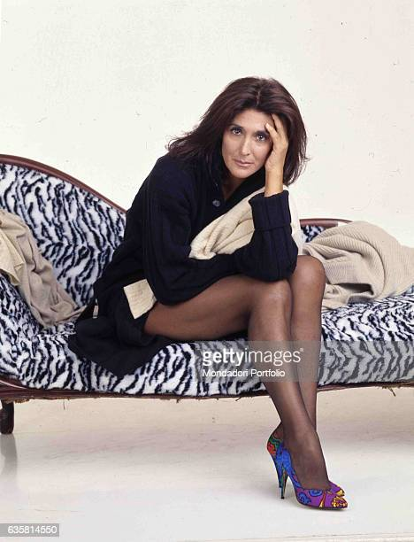 Italian comedian Anna Marchesini posing sitting on a chaise longue for a studio photo shooting. Italy, 1998