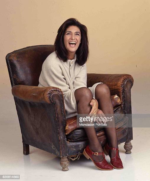 Italian comedian Anna Marchesini posing smiling while sitting on an old leather armchair for a studio photo shooting. Italy, 1998