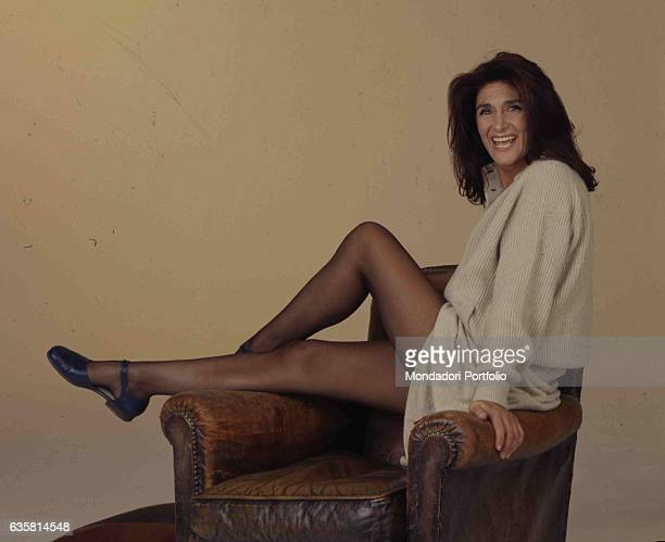 Italian comedian Anna Marchesini posing smiling while sitting on the armrests of an old leather armchair for a studio photo shooting. Italy, 1998