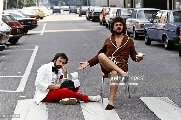 Italian comedian Beppe Grillo wearing a nightgown and holding a coffee cup in his hands and Italian TV author Antonio Ricci with a typewriter on his...