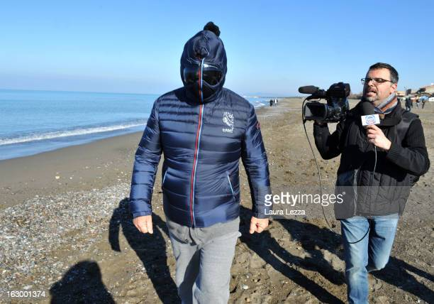 Italian comedian blogger and political leader of the Five Stars Movement Beppe Grillo is questioned as he runs on the beach on March 3 2013 in Marina...