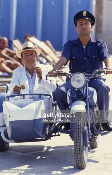 Italian comedian Lino Banfi and Italian actor Maurizio Ferrini as the officer Gino Gridelli on a sidecar in a scene of the film Il commissario Lo...