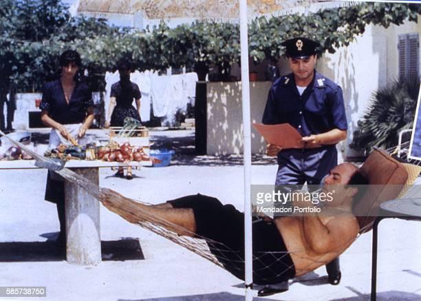 Italian comedian Lino Banfi lying on a hammock in a scene of the film Il commissario Lo Gatto beside Italian actor Maurizio Ferrini as the officer...