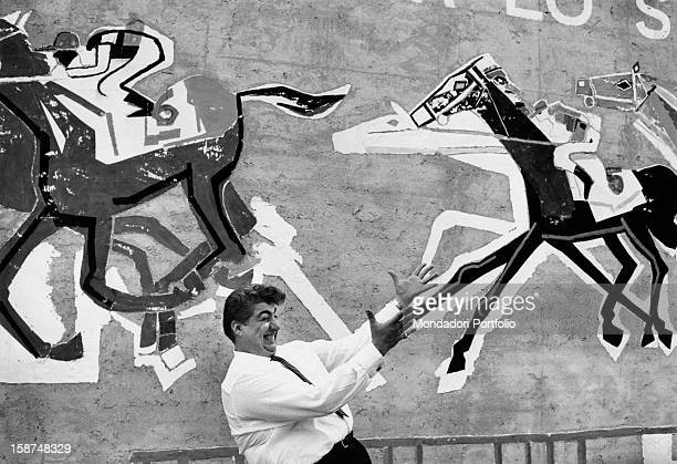 Italian comic actor Gino Bramieri making a face in front of a mural painting depicting some riders by horse at the Trade Fair Milan 1962