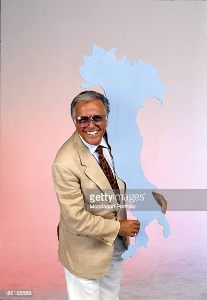 Italian commentator and TV host Gianfranco Funari smiling holding a silhouette of Italian peninsula 1991
