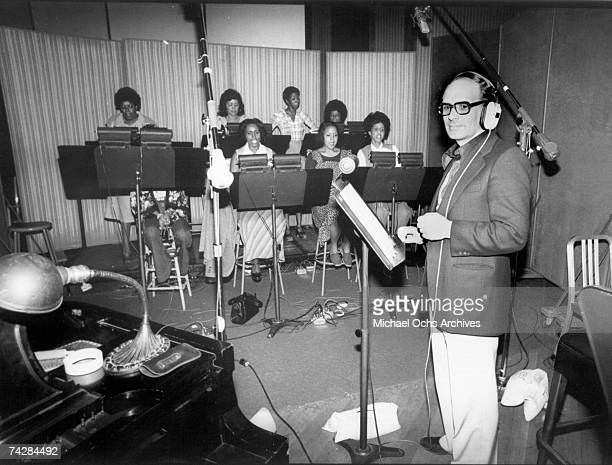 Italian composer arranger and conductor Ennio Morricone records a choral group for the score of the Warner Bros film 'Exorcist II The Heretic' in...