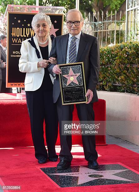 Italian composer Ennio Morricone holds a plaque while posing with his wife Maria Travia on his Star on the Hollywood Walk of Fame during a ceremony...