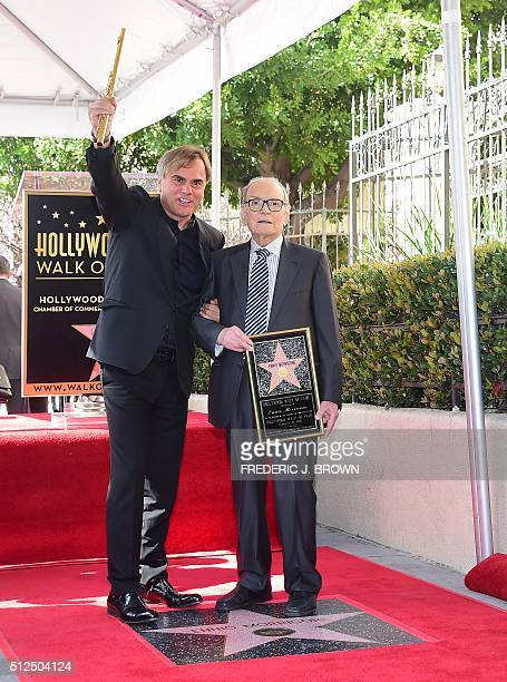 Italian composer Ennio Morricone holds a plaque while posing with flutist Andrea Griminelli on his Star on the Hollywood Walk of Fame during a...