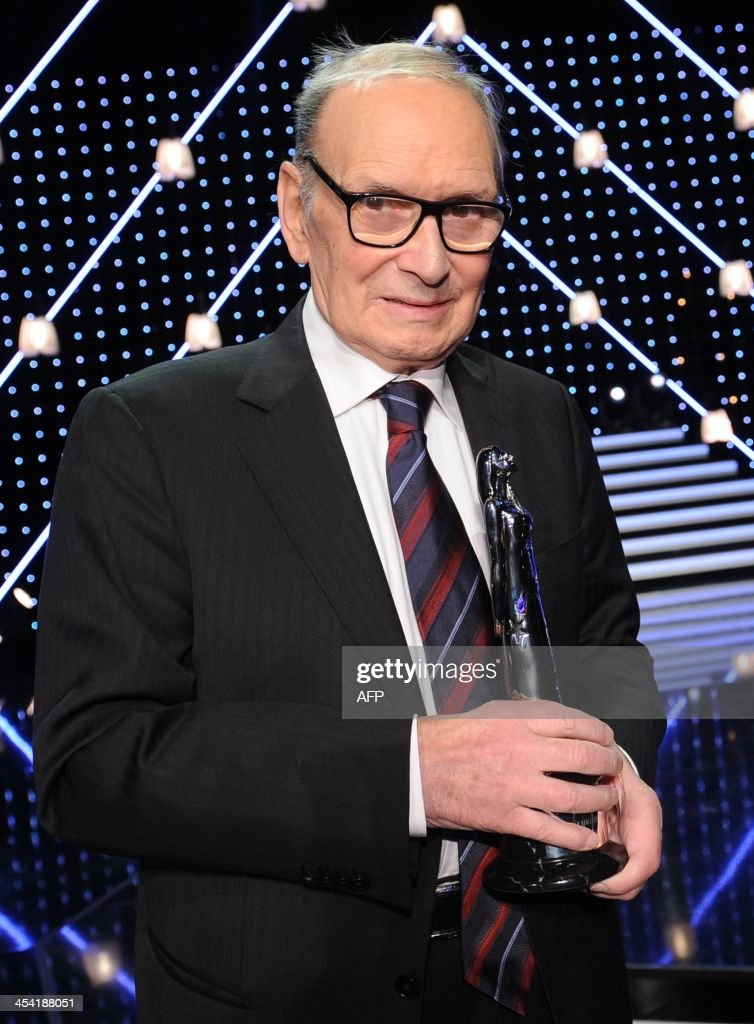 Italian composer Ennio Morricone poses for a photo with his award on stage at the 26th European Film Awards ceremony on December 7, 2013 in Berlin. Every year, the various activities of the European Film Academy culminate in the ceremony of the European Film Awards. In a total of 21 categories, among them European Film, European Director, European Actress and European Actor, the European Film Awards annually honour the greatest achievements in European cinema.