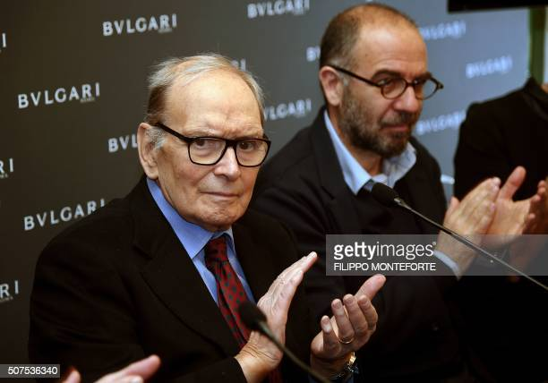 Italian composer orchestrator conductor Ennio Morricone applauds flanked by Italian film director Giuseppe Tornatore after receiving the 2016 Golden...