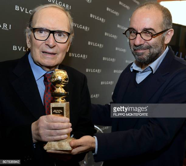 Italian composer orchestrator conductor Ennio Morricone flanked by italian film director Giuseppe Tornatore poses with the 2016 Golden Globe he...