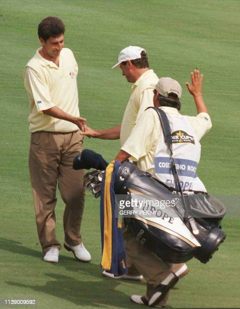 Italian Constantino Rooca and an unidentified caddie congratulates Spaniard Jose Maria Olazabal 26 September after comp[leting an eagle on the 13th...