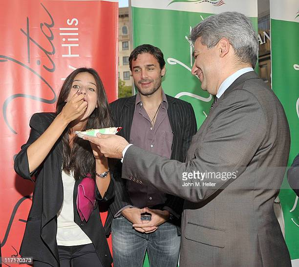 Italian Consul General Nicola Faganello gives actress Katy Saunders a piece of cake while actor Daniele Pecci looks on at La Dolce Vita honoring the...