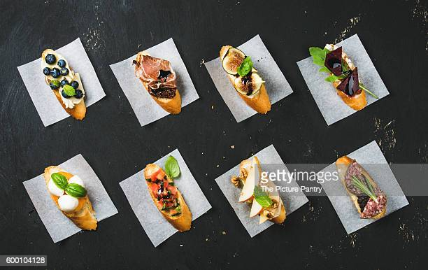 Italian crostini with various toppings on white baking paper over black plywood background