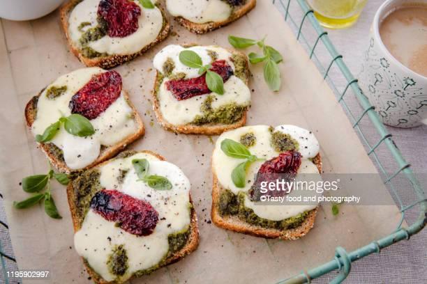 italian cuisine toast made of toasted bread, pesto, mozzarella, dried tomato, basil leaves - pesto stock pictures, royalty-free photos & images