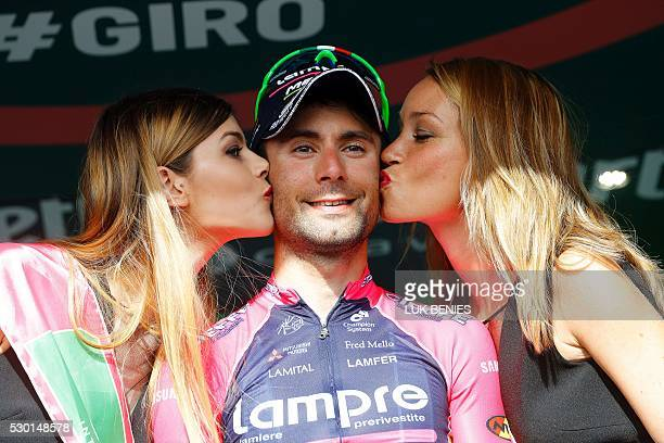 Italian cyclist Diego Ulissi of Lampre - Merida is kissed by hostesses as he celebrates on the podium after winning the fourth stage of 200 km from...