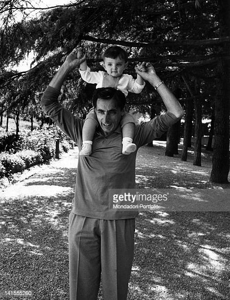 Italian cyclist Fausto Coppi carrying his son Angelo Fausto on his shoulders Novi Ligure June 1956