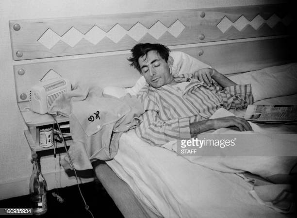 Italian cyclist Fausto Coppi takes a nap next to his yellow jersey as the Tour de France cyclists had a day off 05 July 1952 in the mountain resort...