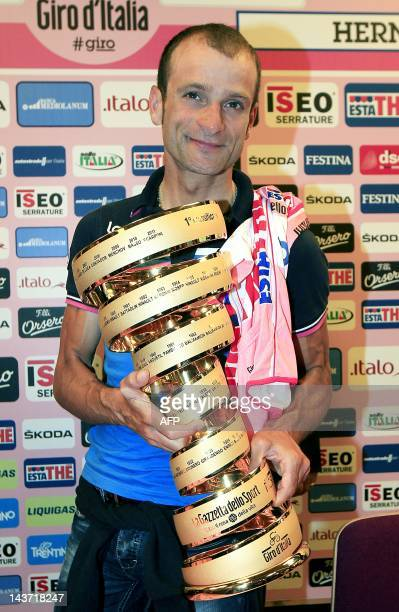 Italian cyclist Michele Scarponi poses his 2011 Tour of Italy trophy after receiving the winner's pink jersey following the disqualification of...