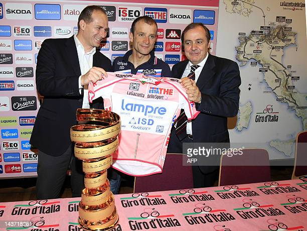 Italian cyclist Michele Scarponi poses with his 2011 Tour of Italy trophy and winner's pink jersey after receiving them from Michele Acquarone...