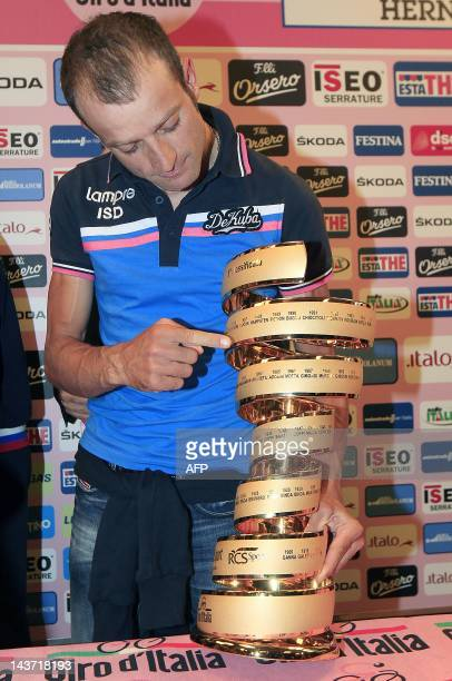 Italian cyclist Michele Scarponi shows his 2011 Tour of Italy trophy after receiving the winner's pink jersey following the disqualification of...