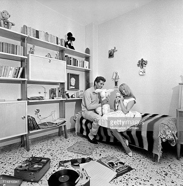 Italian dancers choreographer and actors Elena Sedlak and Paolo Gozlino sitting on the floor listening to some records 1960