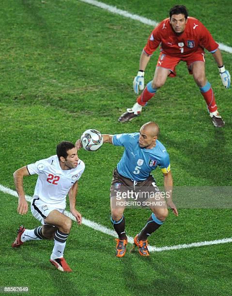 Italian defender Fabio Cannavaro fights for the ball with Egytpian forward Mohamed Aboutrika as Italian goalkeeper Gianluigi Buffon watches during...