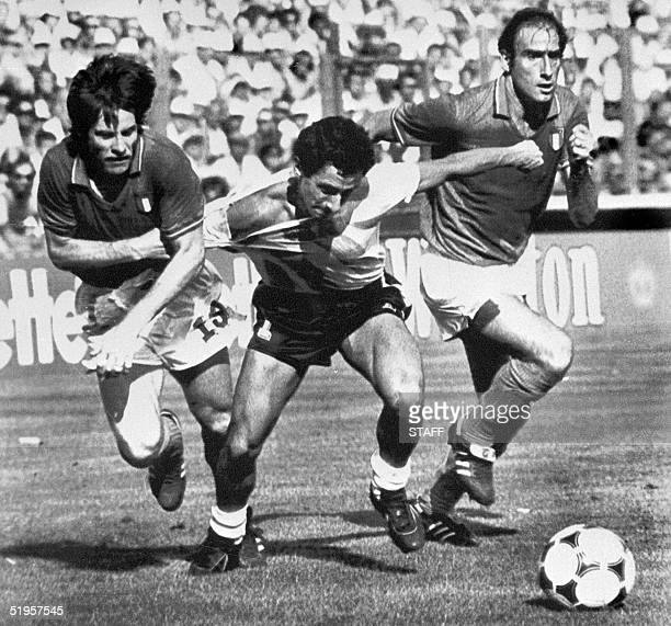 Italian defender Gabriele Oriali pulls the jersey of Argentinian forward Osvaldo Ardiles as he tries to run past forward Francesco Graziani 29 June...