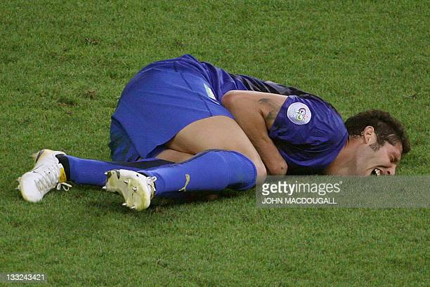 Italian defender Marco Materazzi lies on the pitch after receiving a head butt by French midfielder Zinedine Zidane during the World Cup 2006 final...
